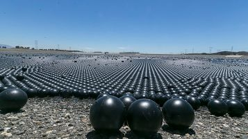 """Over 90 million plastic balls cover the Los Angeles Reservoir in the Sylmar area of Los Angeles Wednesday, Aug. 12, 2015. The city has completed a program of covering open-air reservoirs with floating """"shade balls"""" to protect water quality.  The 4-inch-diameter plastic balls block sunlight from penetrating the 175-acre surface of the reservoir, preventing chemical reactions that can cause algae blooms and other problems.  (AP Photo/Damian Dovarganes)"""